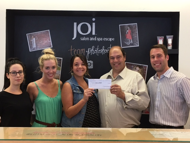 CHECK PRESENTATION: (L) to (R) Molly Pare, Laura, Jessica Winterle – Joi Salon Manager, NEAD President John Romano, John Pregmon NEAD Board Member Joi Salon Manager Jessica Winterle presents NEAD President John Romano with a check for $2064, the proceeds from their Summer of Joi Event Fundraiser.